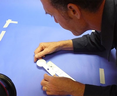 Photograph of a researcher aligning a measuring spoon by using a ruler or straightedge aligned with the tape guide (H) in the previous photo.